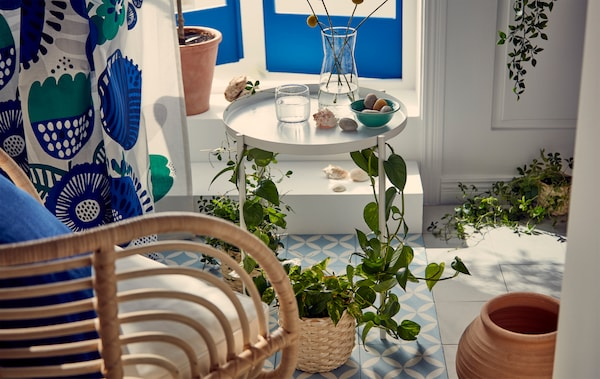 Blues and whites in a sunny spot just inside French balcony-style windows. Wicker armchair beside a plant-wrapped tray table.