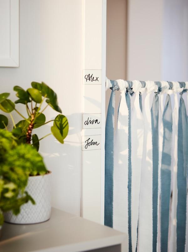 BOTAREN 博塔仁 浴帘杆挂在门口。门框上贴有 IKEA 365+ 标签,上面写有每个人的名字。