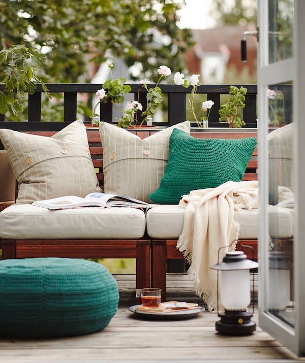 Breakfast on the balcony with open doors and plenty of cushions, blankets and some outdoor furniture.