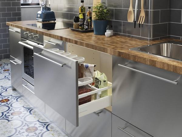 不锈钢厨房岛台和橡木/贴面木质操作台面。一个抽屉敞开,里面装着大量干货。