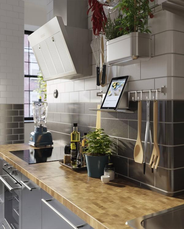 不锈钢厨房岛台、木质台面、新鲜香菜和壁装挂杆,平板支架上摆放着一部平板。
