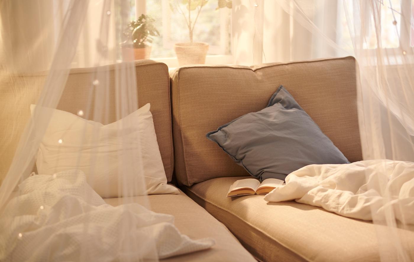 采光充足的窗户旁并排摆放着两张米色 KIVIK 奇维 贵妃椅。贵妃椅上放着床罩和书,上方挂着 SOLIG 索利格 帘帐。