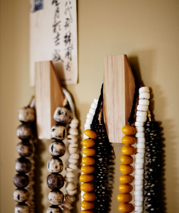 彩色的串珠项链挂在两个木制挂钩上。