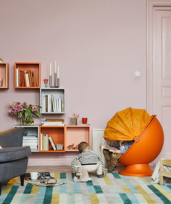 彩色客厅里摆放着一把橙色的儿童蛋形椅,两个孩子正在阅读和游戏。