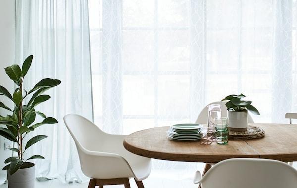 餐厅里摆着一张圆形木桌和几把白色椅子,后面的法式窗户饰有绿色和白色的窗帘。