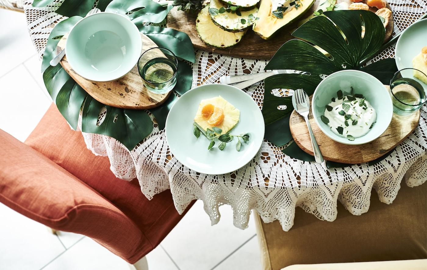 餐桌上摆放着大大的叶子、木板和绿色餐具,餐具里放着水果和酸奶。