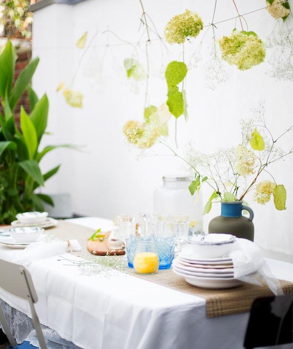 餐桌上摆放着盘子、玻璃杯和一瓶鲜花,美丽的花朵垂悬在上方的绳子上。