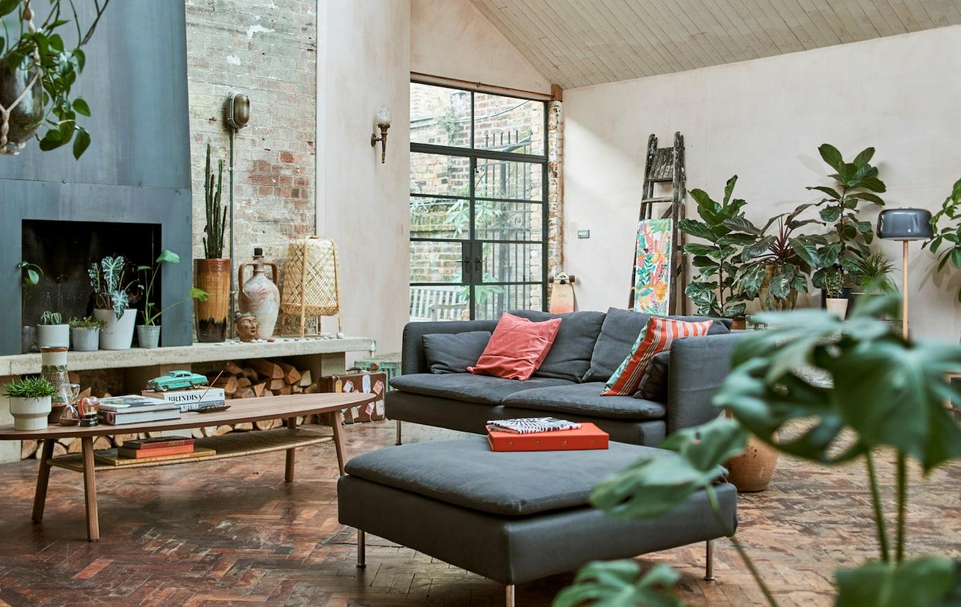 仓库风格的客厅配有砖墙、壁炉、镶木地板、蓝色沙发和脚凳、茶几和植物。
