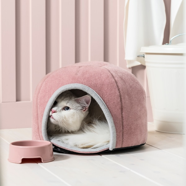 Cat peeking out of round, pouffe-shaped cat house made from soft fabric. A colour-matched pet bowl next to the opening.