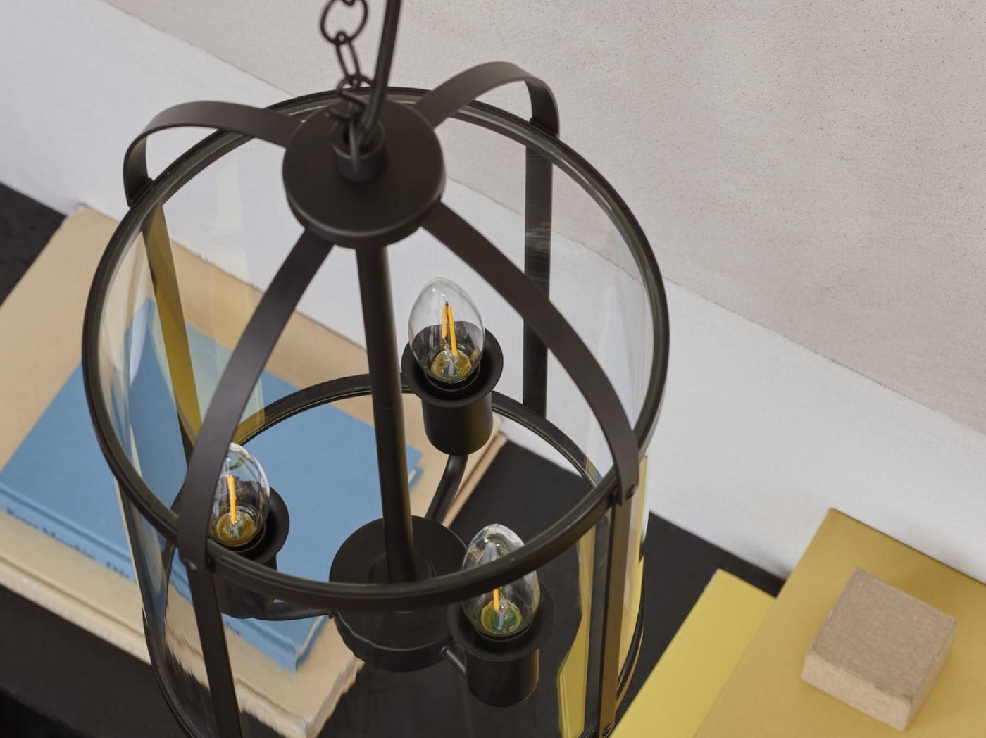产品特写:采用吊挂烛台设计的GALJON 加里恩 吊灯上装有三个装饰灯泡,背景中摆放着五颜六色的书籍。