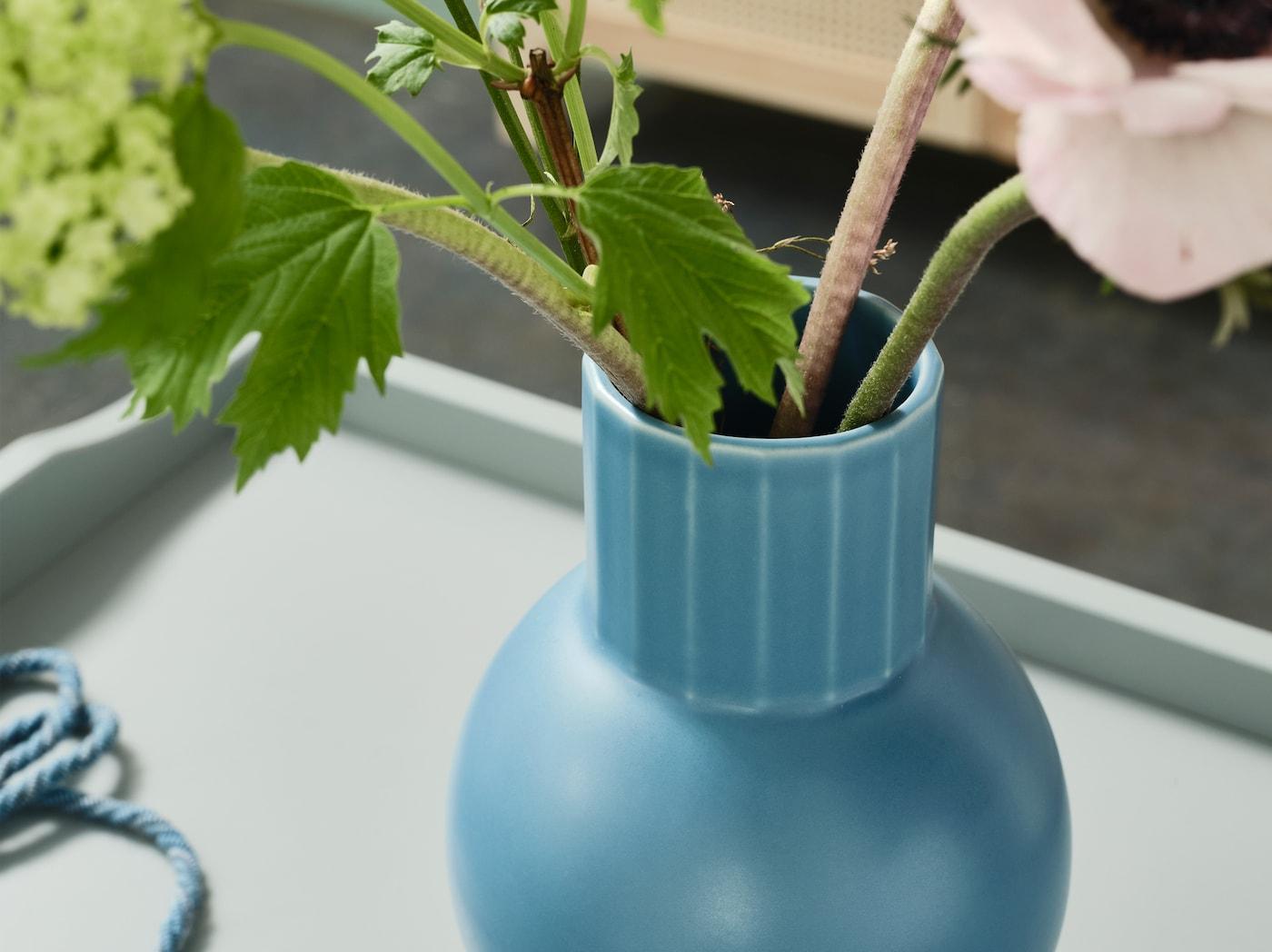 产品特写:一个蓝色OMFÅNG 邬姆芳恩 花瓶静立在一张边桌上,瓶中插着几枝绿色花茎。