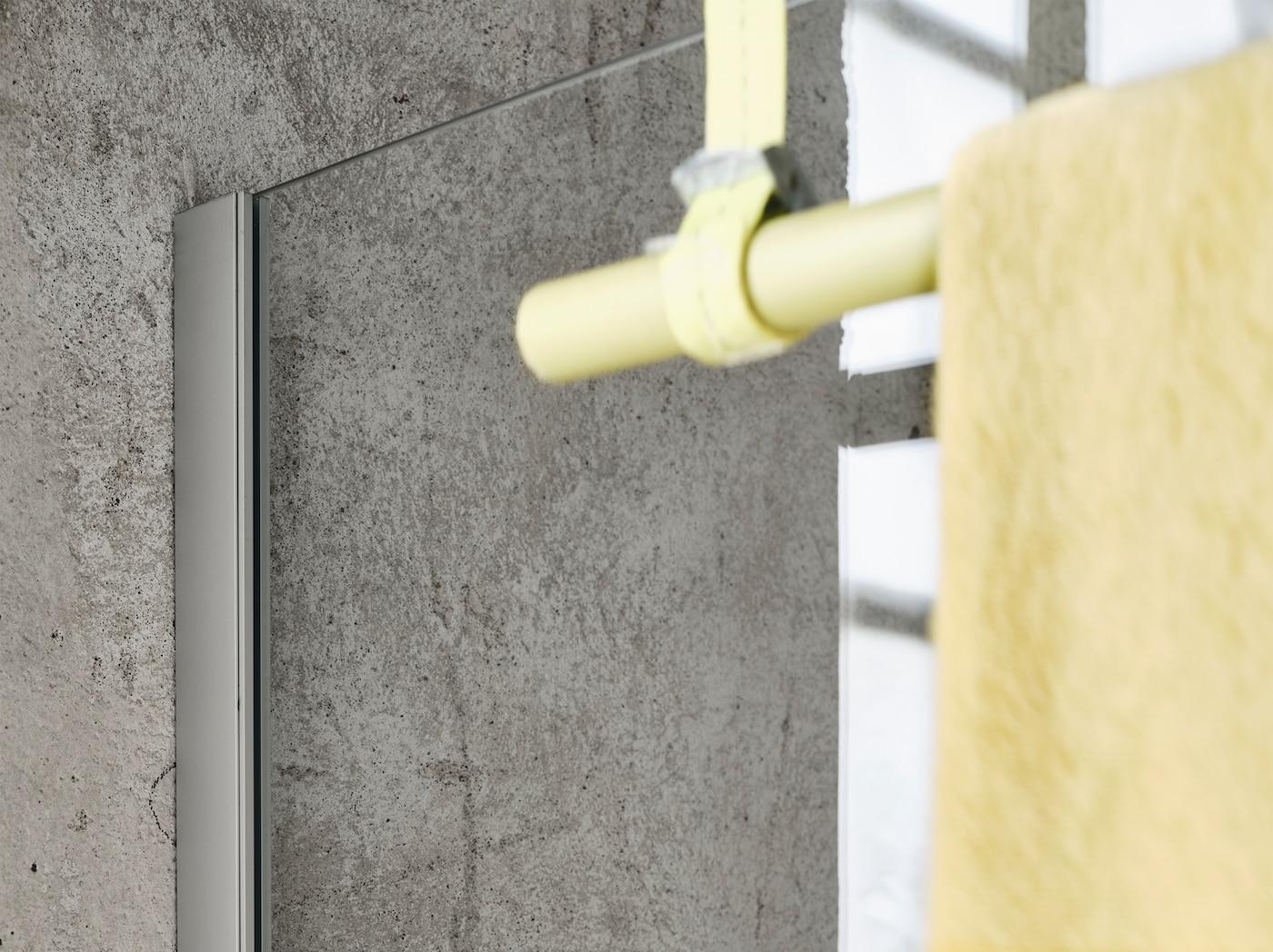 产品特写:一面带有黄色挂杆的OPPEJEN 奥佩耶恩 淋浴隔断固定在灰色混凝土墙面上,前景中还挂着毛巾。