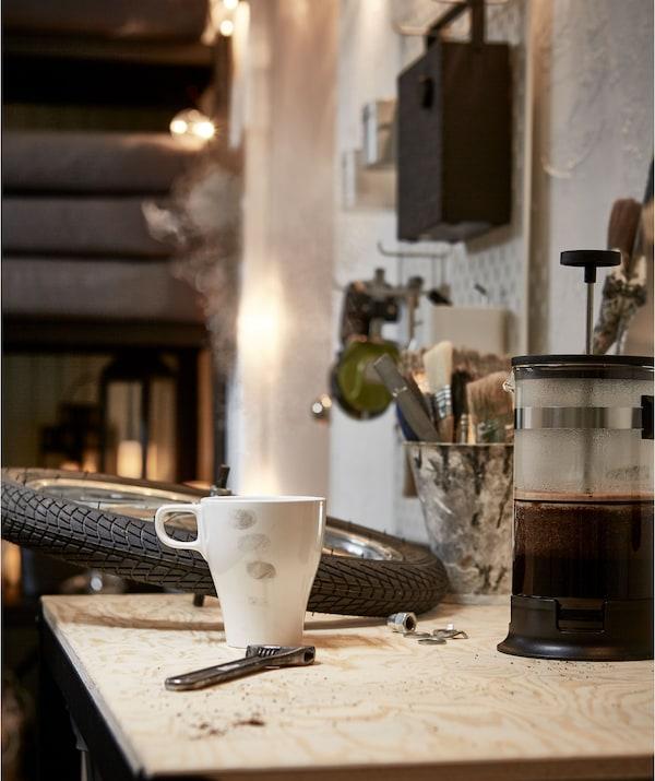 车库风格的房间里,工作台上摆放着车轮、扳手、咖啡机和带污渍的马克杯。
