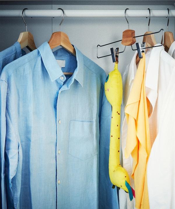 成排的衬衫悬挂在衣柜挂衣杆上。其中一个衣架上夹着一个毛绒玩具和休闲毯。