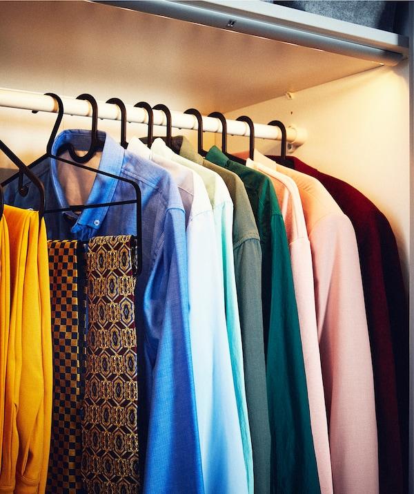 成排挂在衣架上的衬衫和配饰,置于衣柜挂衣杆之上,LED照明条则点亮了隔间空间。