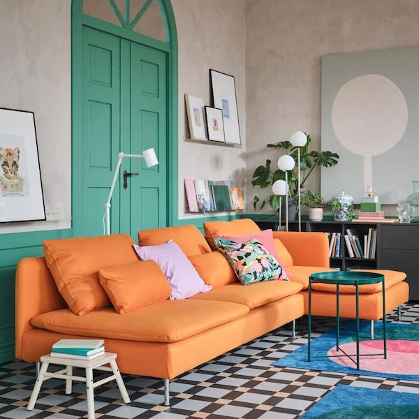 橙色四人沙发和贵妃椅、绿色托盘桌、两张粉色/绿色/蓝色地毯和两盏白色落地灯。