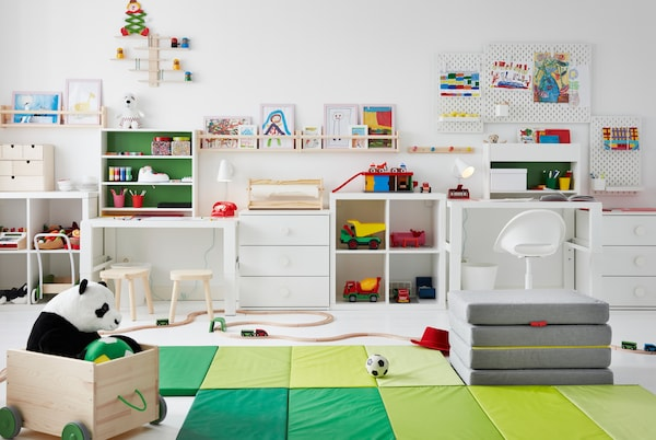Children's room with toys across the floor, desks along the side, and drawings on pegboards and FLISAT ledges up the walls.