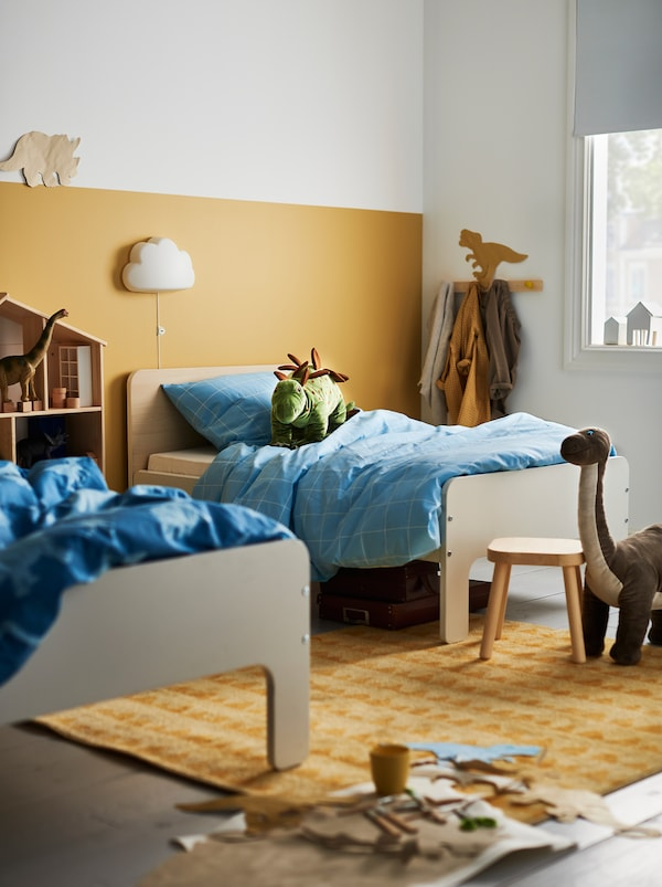 Children's room with two different-length SLÄKT extendable beds standing a few feet apart amid toys and storage.