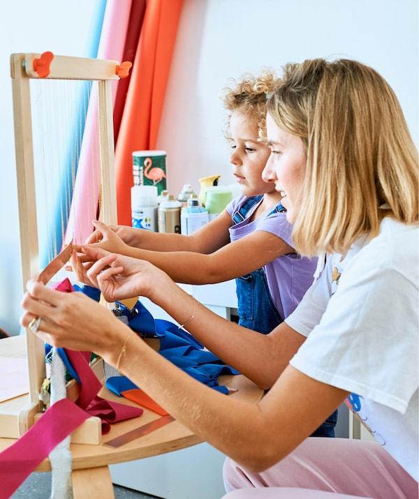 Chloé和女儿在木质织机上编织布条。