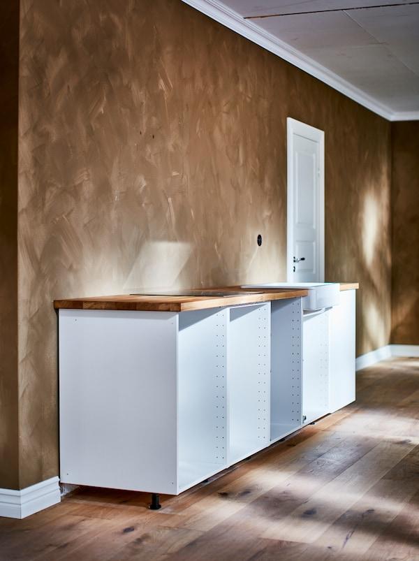 充满笔触纹理的浅褐色墙面前方,摆放着一张白色的METOD 米多 底柜框架。