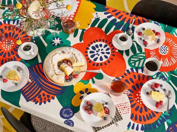 厨房餐桌铺着花朵图案的桌布,放着盘子、玻璃杯、马克杯和蛋糕。