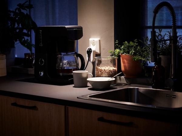 厨房操作台面上放着与可控插头相连的咖啡机,水槽边放着杯子和碗。