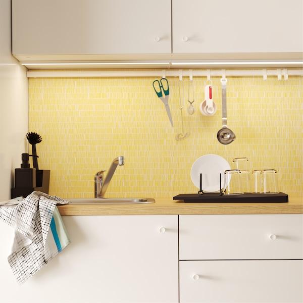 厨房搭配白色柜门、黄色后挡板和带挂钩的挂杆,挂杆上挂有剪刀和其他厨房器具。