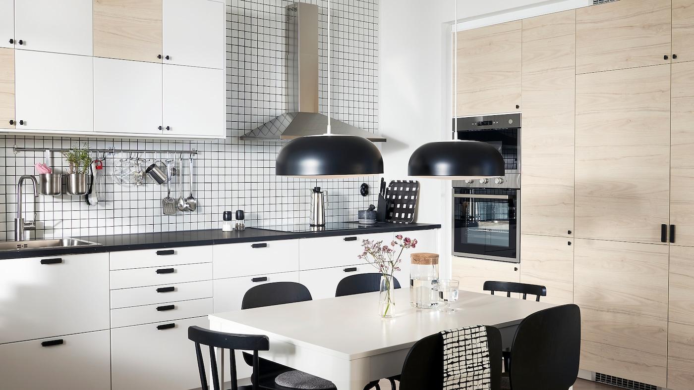 厨房带白色和浅色仿白蜡木柜门、两盏黑色吊灯、一张白色桌子和黑色的椅子。