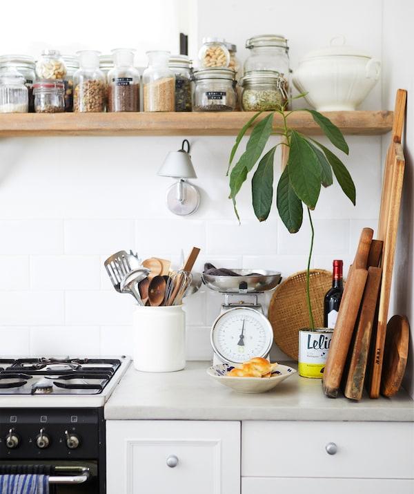 厨房的操作台面上设有炉灶和木板,上方的木质搁板上放着几罐干燥的食材。