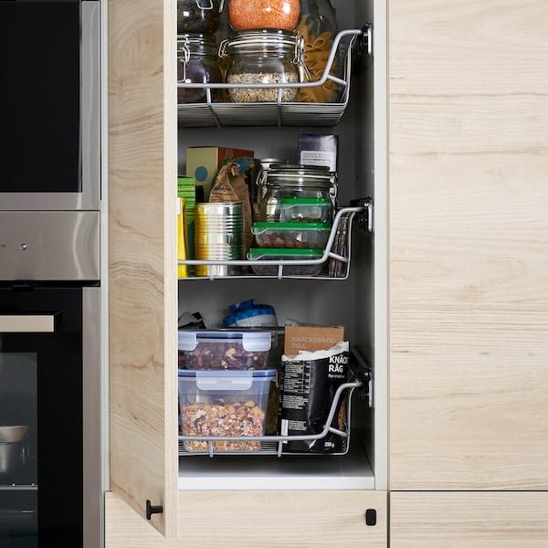 厨房里配有浅色仿白蜡木柜门的高柜开着,展示着里面的金属丝篮、食品盒和其他物品。