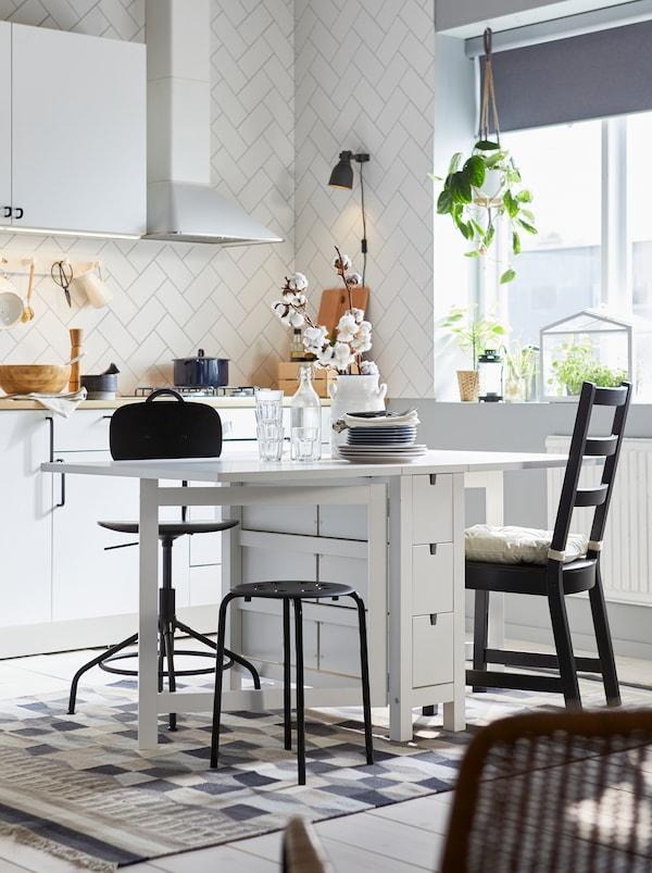 厨房里,一张白色的NORDEN 诺顿 折叠式餐桌,两边的折叶都已展开;周围摆放着款式各异的座椅,包括一张KULLABERG 乐维 椅子。