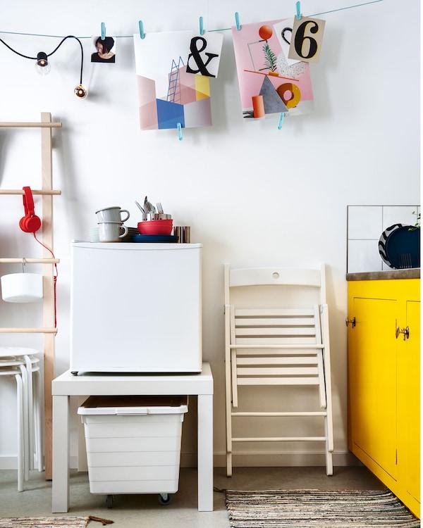 厨房旁边的区域里,一条线上挂着一些墙面装饰。LACK 拉克 桌子上放有一台小型冰箱,桌子下是一个垃圾箱。