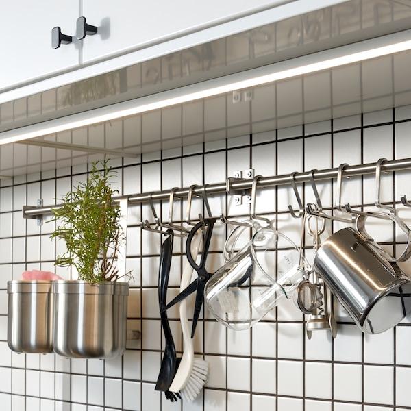 厨房配有白色柜门,下方是白色瓷砖墙,墙上装有带不锈钢挂钩的挂杆。