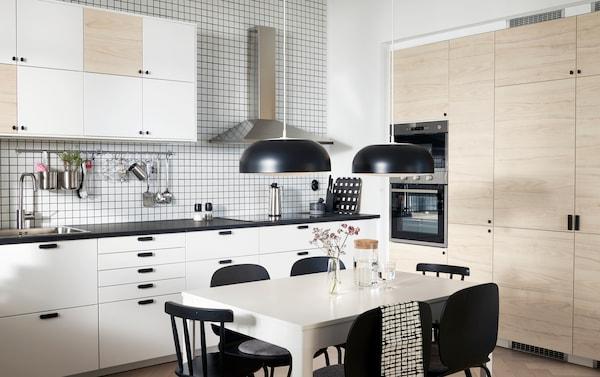 厨房配有白色和浅色仿白蜡木柜门、两盏吊灯、一张白色桌子和几把黑色椅子。