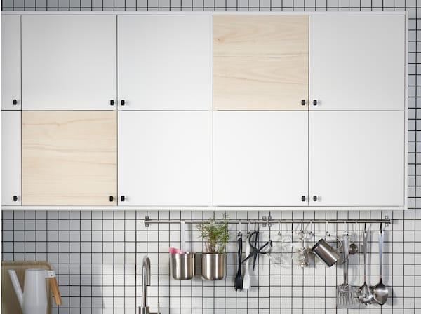厨房配有白色和浅色仿白蜡木柜门、两根不锈钢挂杆和一把白色洒水壶。