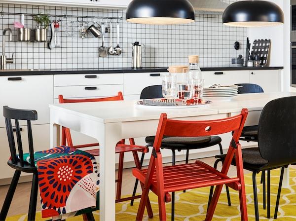 厨房配有白色加长餐桌、红色和黑色椅子、黄色/白色地毯和两盏黑色吊灯。