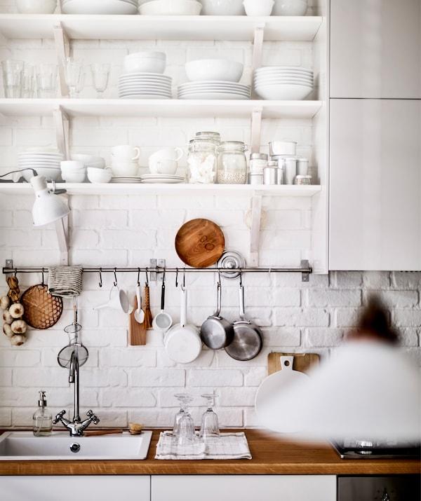 厨房水槽和木质操作台面上方的开放式搁板单元上摆放着白色陶器。