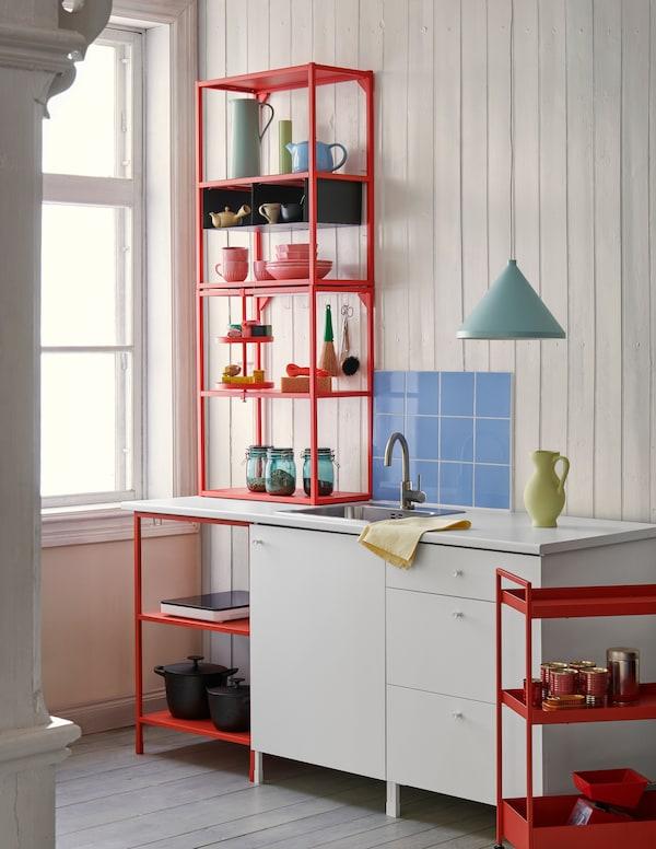 厨房中的带开放和封闭式储物空间的橘红色配白色的ENHET 安纳特 模块中摆放着一些彩色的餐具。