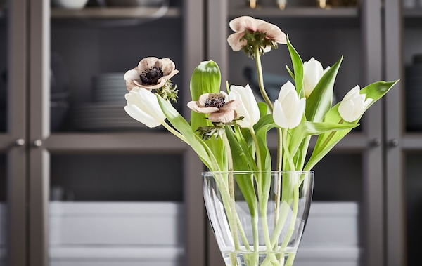 橱柜前摆放着一个弧形VASEN 维森 花瓶,其中插着一小束白色郁金香、褐色罂粟花和鲜嫩的绿叶。