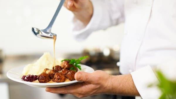 厨师正在讲酱汁淋到肉丸上