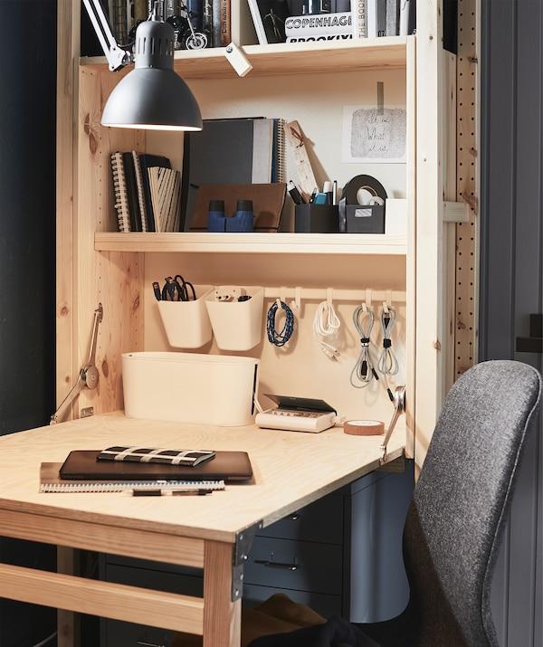储物单元和折叠式桌面组成了小型家庭工作空间。搁板上放着电线和办公用品。