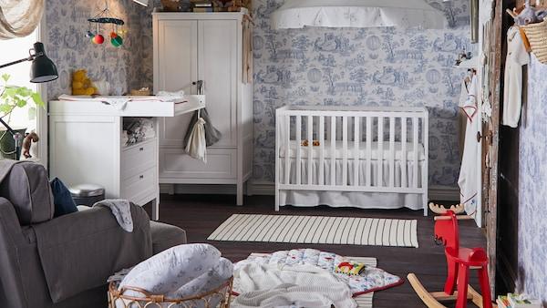 传统风格的儿童房装饰蓝白色壁纸,里面放着SUNDVIK 桑维 婴儿床、衣柜和婴儿换衣桌。