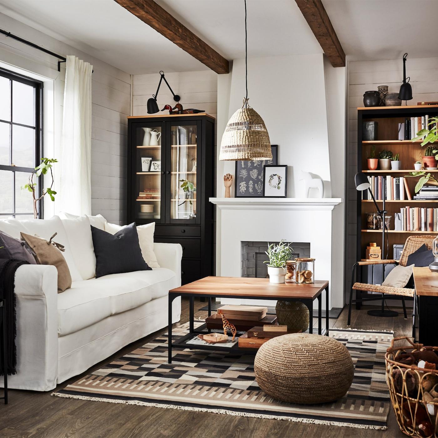传统风格的客厅里摆放着深褐色/实心松木书柜和电视柜,一张白色沙发和一个玻璃门柜。