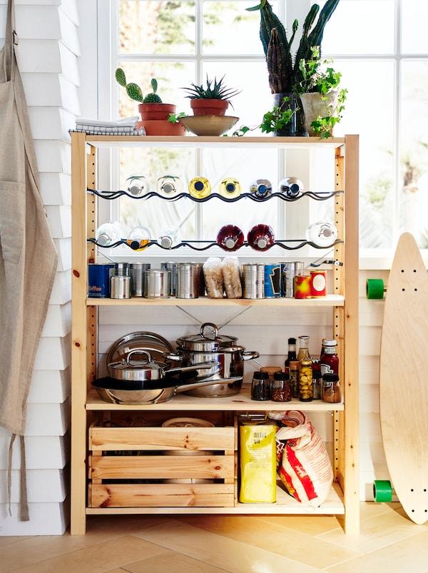 窗边有一个IVAR 伊娃 储物单元,如同一个小食品储藏室,架子上摆放着锅具、干货、罐头食品和各种瓶瓶罐罐。