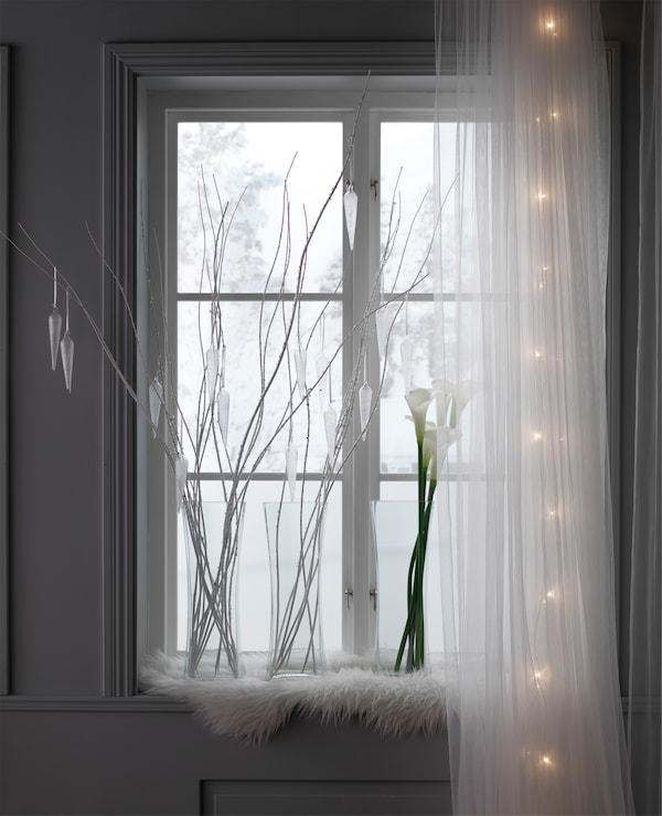 窗边装饰着玻璃花瓶、树枝和马蹄莲,透过窗子,还能看见外面的雪景。