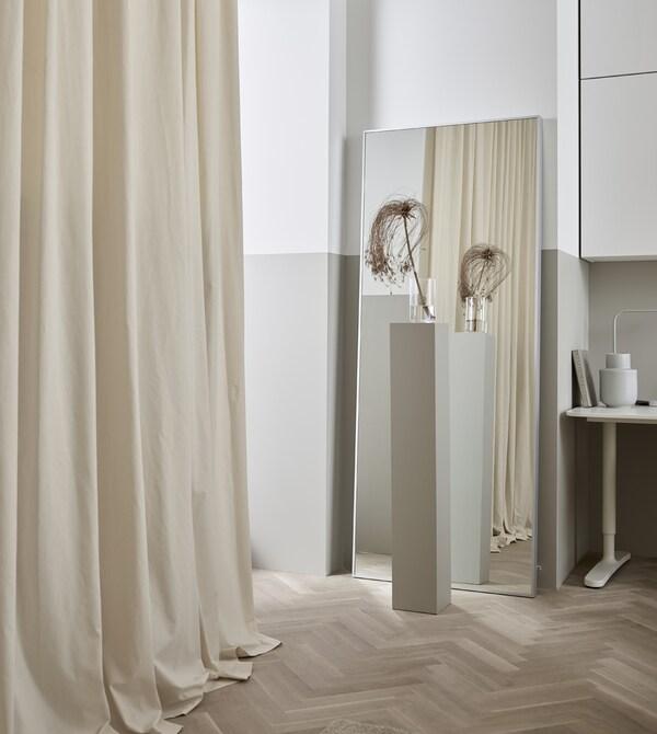 窗帘不一定要用在窗户上。把窗帘挂在空白的墙面上,整个房间会显得更加柔和。
