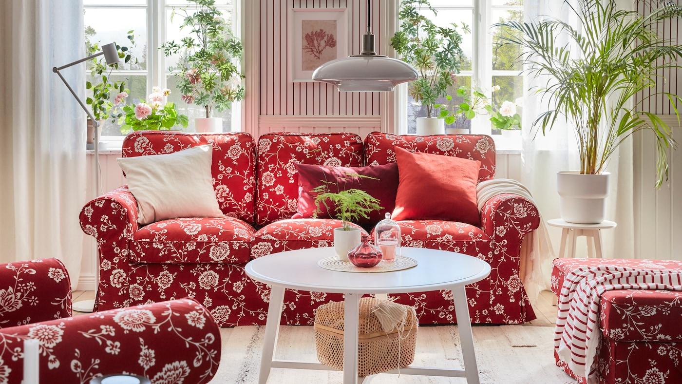 窗前是一张红色沙发,有白色的花卉图案,还有许多绿植、一张白色圆桌和一盏吊灯。