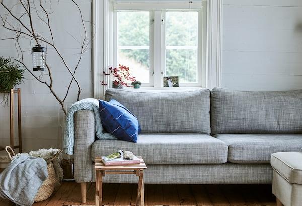 窗前有一张灰色沙发,一旁的篮筐里放着羊毛休闲毯,巨大的玻璃花瓶中放有树枝装饰。