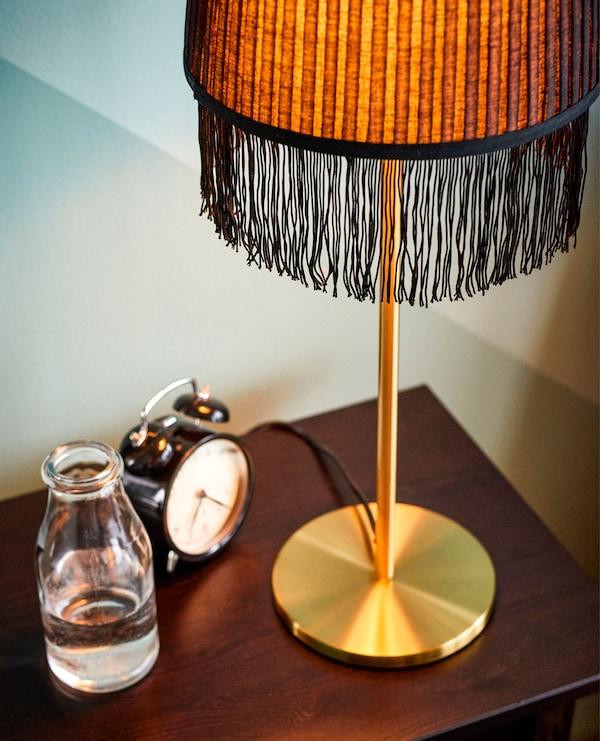 床边桌上摆放着金色带流苏台灯、闹钟和一杯水。