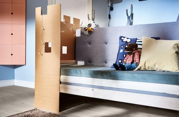 床垫改造的沙发,带靠垫和一张趣味纸板墙